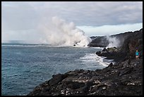 Hiker and volcanic steam cloud on coast. Hawaii Volcanoes National Park, Hawaii, USA. (color)