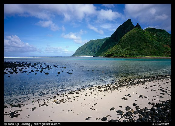 Tropical beach with sand and pebbles, and pointed peaks of Ofu Island. National Park of American Samoa (color)