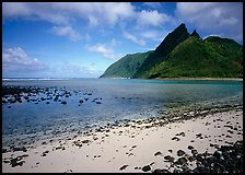 Tropical beach with sand and pebbles, and pointed peaks of Ofu Island. National Park of American Samoa