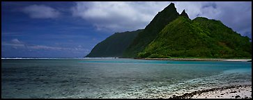 Tropical landscape with blue waters, pointed peaks, and clouds, Ofu Island. National Park of American Samoa (Panoramic color)