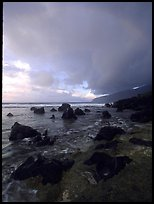 Boulders and coastline at sunrise with rainbow, Siu Point, Tau Island. National Park of American Samoa (color)