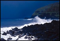 Dark boulders, crashing waves, and dark sky, storm light, Tau Island. National Park of American Samoa