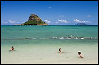 Family in the waters of Kualoa Park with Chinaman's Hat in the background. Oahu island, Hawaii, USA