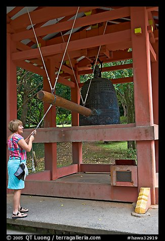 Tourist rings the sacred bell before entering Byodo-In temple. Oahu island, Hawaii, USA (color)