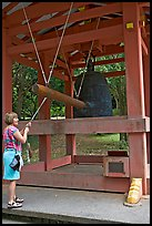 Visitor rings the sacred bell before entering Byodo-In temple. Oahu island, Hawaii, USA