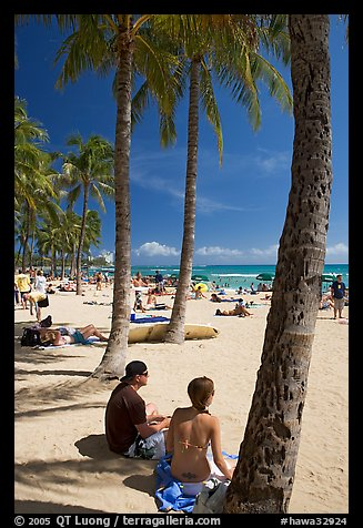 Couple under palm trees on Waikiki beach. Waikiki, Honolulu, Oahu island, Hawaii, USA