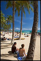 Couple under palm trees on Waikiki beach. Waikiki, Honolulu, Oahu island, Hawaii, USA (color)