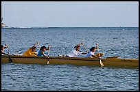 Young women padding a hawaiian outrigger canoe, Maunalua Bay, late afternoon. Oahu island, Hawaii, USA