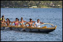Outrigger canoe paddled by women in bikini, Maunalua Bay, late afternoon. Oahu island, Hawaii, USA (color)