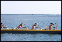 Side view of women in bikini paddling a outrigger canoe, Maunalua Bay, late afternoon. Oahu island, Hawaii, USA
