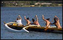 Back view of women in bikini paddling a outrigger canoe, Maunalua Bay, late afternoon. Oahu island, Hawaii, USA (color)