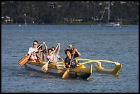 Boys paddling an outrigger canoe, Maunalua Bay, late afternoon. Oahu island, Hawaii, USA (color)