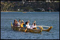 Girls paddling an outrigger canoe, Maunalua Bay, late afternoon. Oahu island, Hawaii, USA