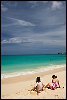 Young women sitting on Waimanalo Beach. Oahu island, Hawaii, USA (color)