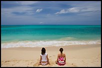 Young women facing the Ocean in a meditative pose on Waimanalo Beach. Oahu island, Hawaii, USA