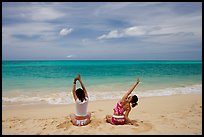 Young women stretching on Waimanalo Beach. Oahu island, Hawaii, USA