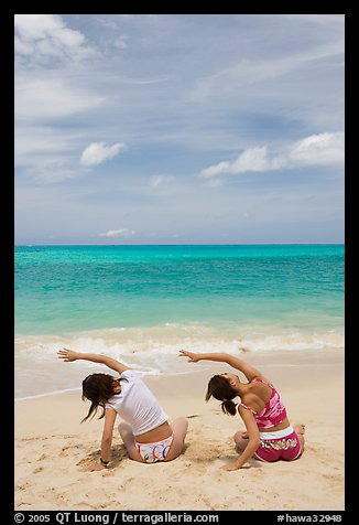 Young women doing gymnastics on Waimanalo Beach. Oahu island, Hawaii, USA (color)