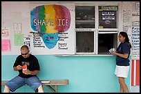 Shave ice store with man sitting eating and woman ordering, Waimanalo. Oahu island, Hawaii, USA