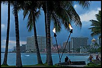 Waterfront at dusk with bare flame lamps. Waikiki, Honolulu, Oahu island, Hawaii, USA