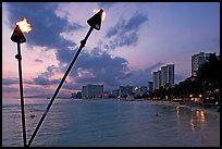 Bare flame torches and skyline at sunset. Waikiki, Honolulu, Oahu island, Hawaii, USA (color)