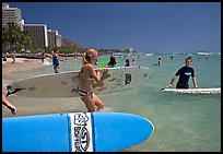 Surfers entering the water with boards, Waikiki Beach. Waikiki, Honolulu, Oahu island, Hawaii, USA (color)