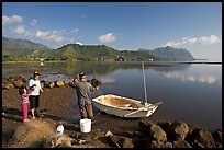 Fisherman and family pulling out net out of small baot, Kaneohe Bay, morning. Oahu island, Hawaii, USA