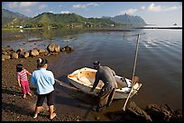 Fisherman and family pulling out net out of small baot, Kaneohe Bay, morning. Oahu island, Hawaii, USA ( color)