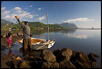 Fisherman pulling out fish out a net, with girl looking, Kaneohe Bay, morning. Oahu island, Hawaii, USA