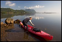 Man loading sea kayak for a fishing trip, Kaneohe Bay, morning. Oahu island, Hawaii, USA
