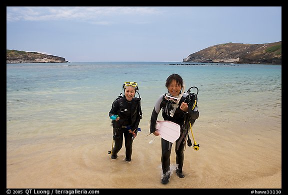 Scuba divers walking out of the water, Hanauma Bay. Oahu island, Hawaii, USA (color)