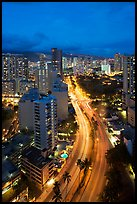 Boulevard and high rise buildings at dusk. Waikiki, Honolulu, Oahu island, Hawaii, USA