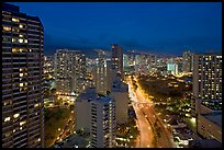 Boulevard and high-rise towers at dusk. Waikiki, Honolulu, Oahu island, Hawaii, USA