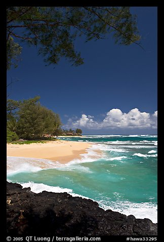 Beach, volcanic rock, and turquoise waters, and homes  near Haena. North shore, Kauai island, Hawaii, USA (color)