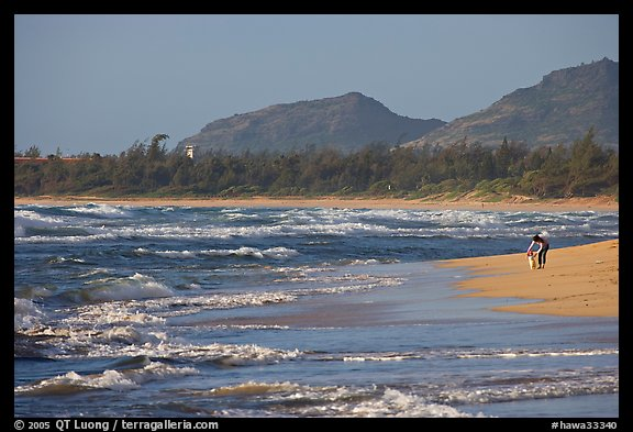 Woman with child on beach, Lydgate Park, early morning. Kauai island, Hawaii, USA (color)