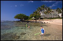 Children on Puu Poa Beach and Princeville Hotel. Kauai island, Hawaii, USA (color)