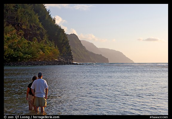 Couple standing in water, Kee Beach, late afternoon. Kauai island, Hawaii, USA
