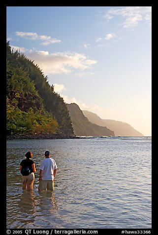 Couple looking at the Na Pali Coast, Kee Beach, late afternoon. Kauai island, Hawaii, USA (color)