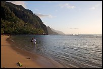 Couple standing in water looking at the Na Pali Coast, Kee Beach, late afternoon. Kauai island, Hawaii, USA