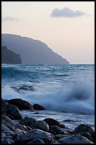Boulders, waves, and Na Pali cliffs, sunset. Kauai island, Hawaii, USA