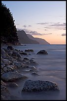 Boulders, surf, and Na Pali Coast, sunset. Kauai island, Hawaii, USA