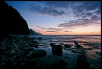 Boulders, surf, and Na Pali Coast, dusk. Kauai island, Hawaii, USA