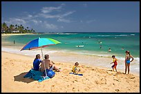 Couple sitting under sun unbrella with children playing around, Poipu Beach, mid-day. Kauai island, Hawaii, USA (color)
