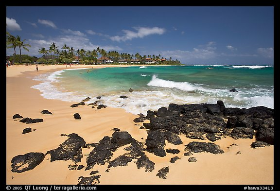 Dark rocks and Kiahuna Beach, mid-day. Kauai island, Hawaii, USA