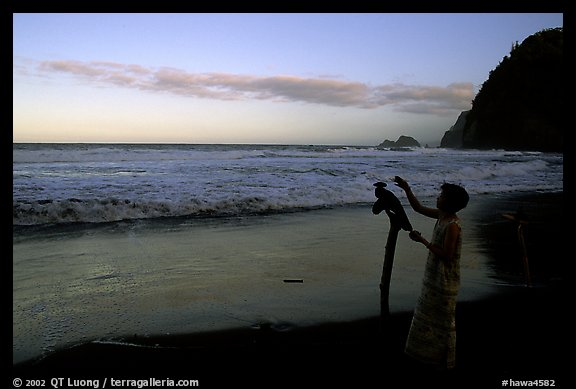 Hawaiian woman piles a stone on a stick as a traditional gesture of reverence, Polulu Beach. Big Island, Hawaii, USA