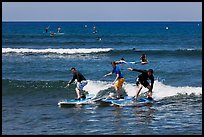 Surfing students ride the same wave. Lahaina, Maui, Hawaii, USA