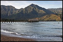 Hanalei Pier and surfer, early morning. Kauai island, Hawaii, USA