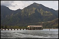 Hanalei Pier, mountains, and surfer. Kauai island, Hawaii, USA
