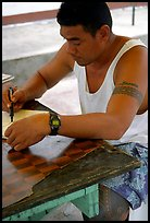 Young man drawing an artwork based on traditional siapo designs. Pago Pago, Tutuila, American Samoa (color)