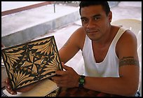 Young man showing an artwork based on traditional siapo designs. Pago Pago, Tutuila, American Samoa (color)