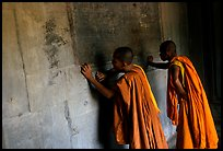 Two buddhist monks examine  bas-reliefs in Angkor Wat. Angkor, Cambodia